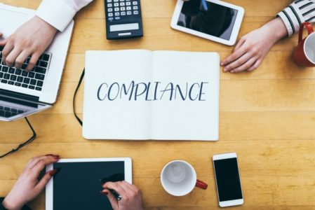 compliance-headline-on-paper-notebook-at-small-business-office-desk-with-young-adult-workers_t20_yw4OE9